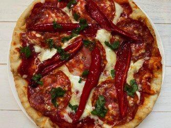 Pizza met pikante salami en geroosterde paprika