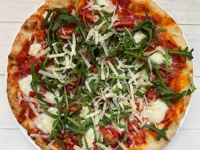 Pizza met tomaatjes, rucola en Grana Padano