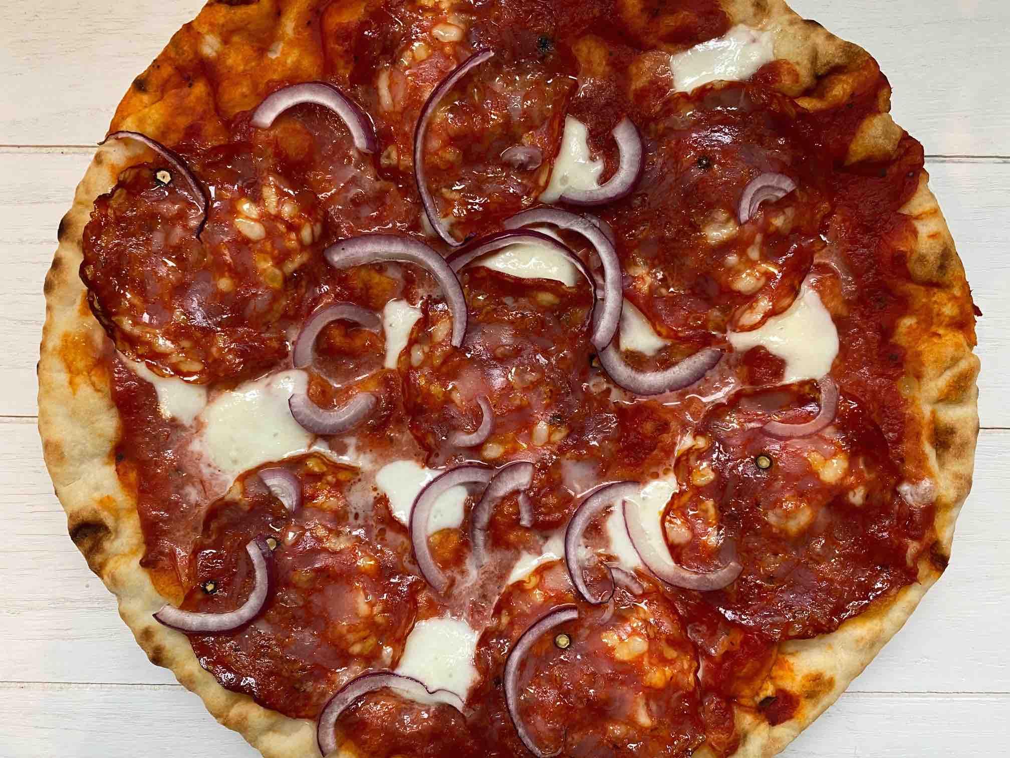 Pizza met pikante salami en rode ui